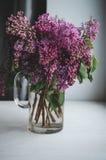 Todavía la vida con las ramas florecientes de la primavera de la lila florece en el florero, fondo oscuro Decoración casera en un Imagen de archivo