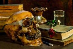 Todavía la vida con los vidrios que llevaban de un cráneo y subió Foto de archivo libre de regalías