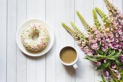 Todavía la vida con una taza de café y de lupine florece el buñuelo en una tabla de madera ligera Copie el espacio Fotos de archivo