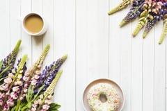 Todavía la vida con una taza de café y de lupine florece el buñuelo en una tabla de madera ligera Copie el espacio Fotografía de archivo