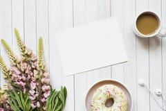 Todavía la vida con una taza de café y de lupine florece el buñuelo en una tabla de madera ligera Copie el espacio Fotografía de archivo libre de regalías