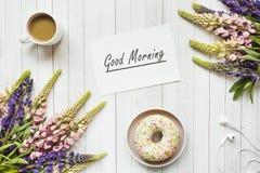 Todavía la vida con una taza de café y de lupine florece el buñuelo en una tabla de madera ligera Copie el espacio Foto de archivo libre de regalías