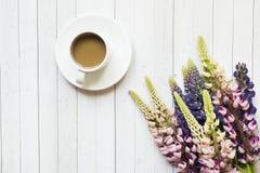 Todavía la vida con una taza de café y de lupine florece el buñuelo en una tabla de madera ligera Copie el espacio Imagen de archivo libre de regalías