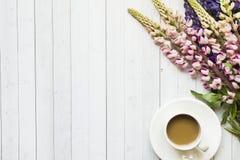 Todavía la vida con una taza de café y de lupine florece el buñuelo en una tabla de madera ligera Copie el espacio Fotos de archivo libres de regalías