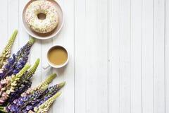 Todavía la vida con una taza de café y de lupine florece el buñuelo en una tabla de madera ligera Copie el espacio Imágenes de archivo libres de regalías