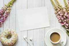Todavía la vida con una taza de café y de lupine florece la libreta del buñuelo en una tabla de madera ligera Copie el espacio Imagenes de archivo