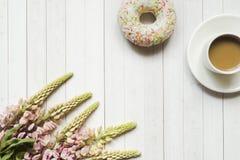 Todavía la vida con una taza de café y de lupine florece la libreta del buñuelo en una tabla de madera ligera Copie el espacio Fotografía de archivo