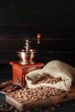 Todavía la vida de los granos de café en yute empaqueta con la amoladora de café Imagenes de archivo