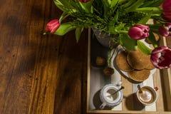 Todavía la vida de tulipanes y del jarabe holandeses se enrolla en una bandeja w de la porción Imagen de archivo libre de regalías