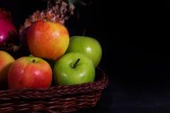 Todavía manzanas de la vida con la cesta de bambú en backgound negro Fotos de archivo