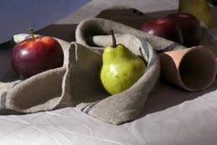 Todavía manzanas y pera rojas de la vida en paño en la tabla fotografía de archivo