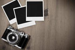 Todavía marcos inmediatos en blanco de la foto de la vida tres en viejo fondo de madera con la cámara retra vieja del vintage con Fotografía de archivo