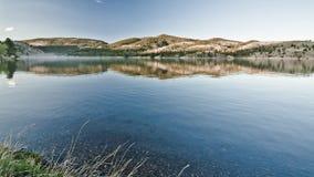 Todavía montañas reflectoras del lago Foto de archivo