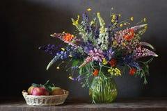 Todavía ramo de la vida con lupine y ranúnculos en un florero de cristal Imagen de archivo libre de regalías
