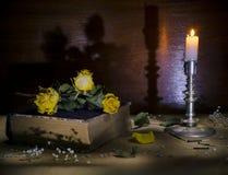 Todavía rosas amarillas viejas de la vida que mienten en el libro, una palmatoria con una vela ardiente Imagen de archivo libre de regalías