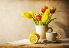 Todavía taza de los tulipanes del amarillo del ramo de la vida de té Imagen de archivo libre de regalías