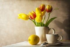 Todavía taza de los tulipanes del amarillo del ramo de la vida de té Foto de archivo libre de regalías