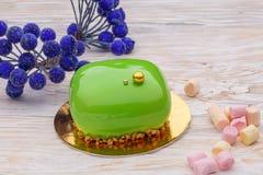 Todavía torta verde de la crema batida de la vida con la melcocha sobre bayas azules del azúcar del und de madera blanco del fond Imagenes de archivo