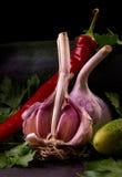 Todavía vida con ajo, pimienta y el pepino. Imagen de archivo libre de regalías