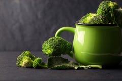 Todavía vida con bróculi verde fresco en taza de cerámica en sto negro Fotografía de archivo libre de regalías