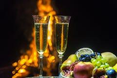 Todavía vida con champán en el fondo del fuego Fotos de archivo