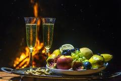 Todavía vida con champán en el fondo del fuego Fotografía de archivo libre de regalías