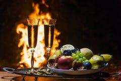 Todavía vida con champán en el fondo del fuego Foto de archivo