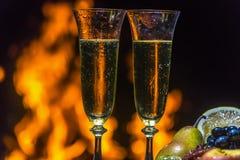 Todavía vida con champán en el fondo del fuego Imágenes de archivo libres de regalías
