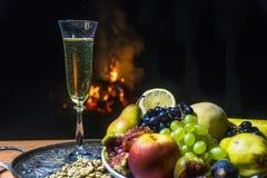 Todavía vida con champán en el fondo del fuego Foto de archivo libre de regalías