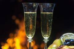 Todavía vida con champán en el fondo del fuego Imagenes de archivo