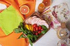 Todavía vida con cortar de la salchicha y del jamón de los cortes fríos, verduras y verdes, aperitivo Imagen de archivo