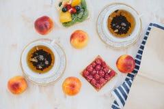 Todavía vida con dos tazas de té en tazas de un vintage y dos tartas con las frutas frescas en un fondo blanco del vintage Imagen de archivo libre de regalías