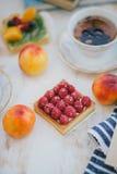 Todavía vida con dos tazas de té en tazas de un vintage y dos tartas con las frutas frescas en un fondo blanco del vintage Foto de archivo