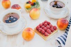 Todavía vida con dos tazas de té en tazas de un vintage y dos tartas con las frutas frescas en un fondo blanco del vintage Fotos de archivo libres de regalías