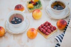 Todavía vida con dos tazas de té en tazas de un vintage y dos tartas con las frutas frescas en un fondo blanco del vintage Fotografía de archivo