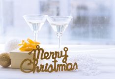 Todavía vida con dos vidrios, la inscripción de la Feliz Navidad y una caja de regalo Fotos de archivo libres de regalías