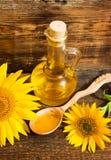 Todavía vida con el aceite vegetal en una botella y girasoles Foto de archivo