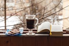 Todavía vida con el café y los dulces, tubo que fuma y libro, para una estancia cómoda en el balcón imagen de archivo