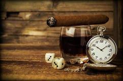 Todavía vida con el coñac, el cigarro, dados y un reloj Fotos de archivo libres de regalías