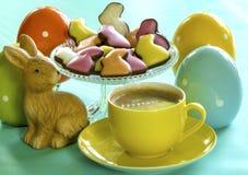 Todavía vida con el conejito de pascua, la taza de café, los caramelos y los huevos de cerámica Fotos de archivo libres de regalías