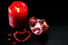 Todavía vida con el corazón rojo de la vela y de la granada Concepto romant Imagenes de archivo