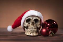 Todavía vida con el cráneo de Papá Noel y las bolas rojas de la Navidad Foto de archivo libre de regalías