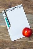 Todavía vida con el cuaderno y la manzana Fotografía de archivo libre de regalías