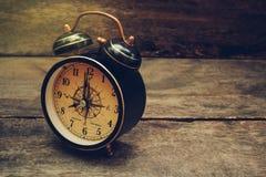 Todavía vida con el despertador en la tabla de madera Fotografía de archivo
