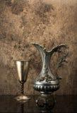 Todavía vida con el jarro antiguo para el vino y un cubilete de plata Imagenes de archivo