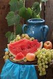 Todavía vida con el jarro, la sandía y las uvas azules Imagen de archivo