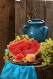 Todavía vida con el jarro, la sandía y las uvas azules Imágenes de archivo libres de regalías