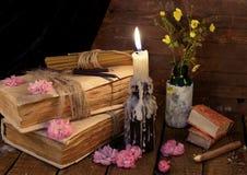 Todavía vida con el libro viejo, la vela ardiente y las flores Fotos de archivo libres de regalías