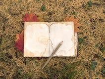 Todavía vida con el libro y las hojas de arce abiertos Imagen de archivo