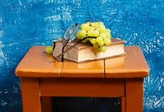 Todavía vida con el libro y las uvas Imagen de archivo libre de regalías